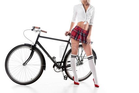 cropped shot of seductive woman on college uniform with bicycle posing isolated on white