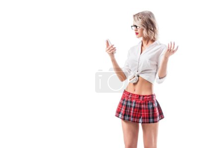 portrait of sexy blond woman in schoolgirl uniform using smartphone isolated on white