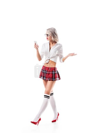 sexy blond woman in schoolgirl uniform using smartphone isolated on white