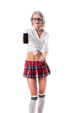 young woman in seductive schoolgirl clothing showing smartphone with blank screen isolated on white