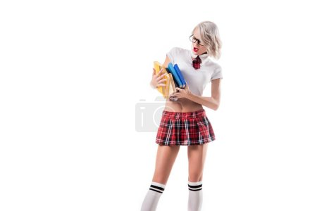 sexy blond woman in schoolgirl clothing holding pile of books isolated on white