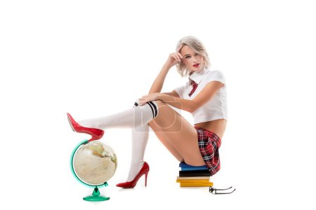 young sexy woman in schoolgirl uniform sitting on pile of books with leg on globe isolated on white