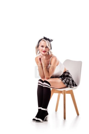 smiling blond woman in short plaid skirt and knee socks sitting on chair isolated on white