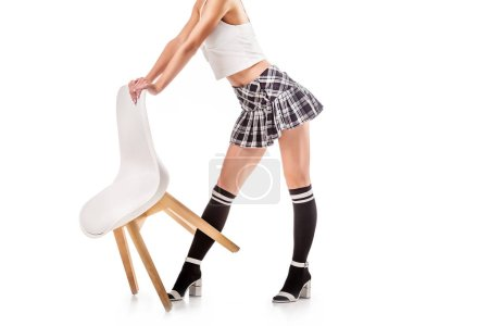 partial view of seductive woman in college uniform standing near chair isolated on white