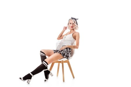 young blond woman in sexy short plaid skirt and knee socks sitting on chair isolated on white
