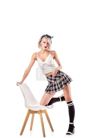 sexy woman in schoolgirl clothing and knee socks on chair isolated on white