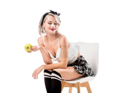Photo for Young sexy woman in short plaid skirt and knee socks with apple in hand sitting on chair isolated on white - Royalty Free Image