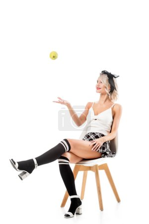 young sexy woman in short plaid skirt and knee socks throwing apple while sitting on chair isolated on white