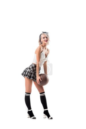 seductive woman in short schoolgirl skirt and black knee socks with basketball ball isolated on white