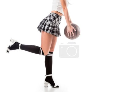 partial view of seductive woman in short schoolgirl skirt and black knee socks with basketball ball isolated on white