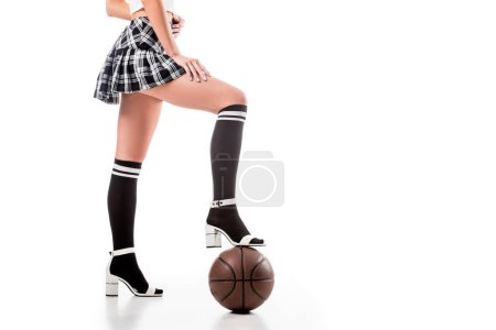 partial view of seductive woman in short schoolgirl skirt with basketball ball isolated on white