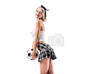 side view of sexy woman in plaid schoolgirl skirt with football ball isolated on white