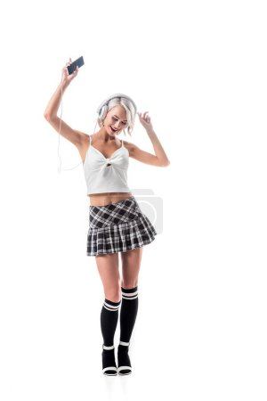 smiling seductive schoolgirl with smartphone listening music in headphones isolated on white