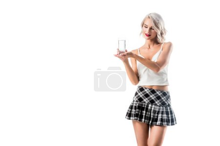 portrait of blond seductive woman in college uniform showing glass of water isolated on white