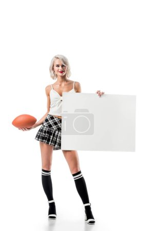 sexy blond woman in short plaid skirt with rugby ball and empty banner posing isolated on white