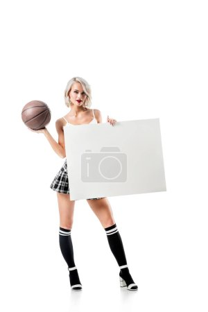 sexy blond woman in short plaid skirt with basketball ball and empty banner posing isolated on white
