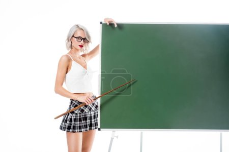 Photo for Young sexy woman in school skirt pointing at empty chalkboard with pointer isolated on white - Royalty Free Image