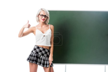 portrait of smiling woman in sexy schoolgirl clothing with pointer showing thumb up at empty chalkboard isolated on white