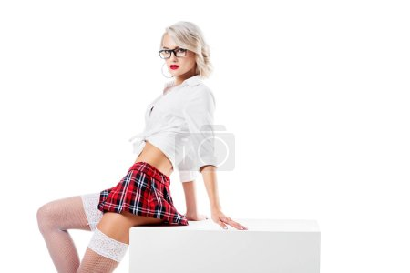 seductive woman in white shirt and plaid schoolgirl skirt sitting on white cube isolated on white