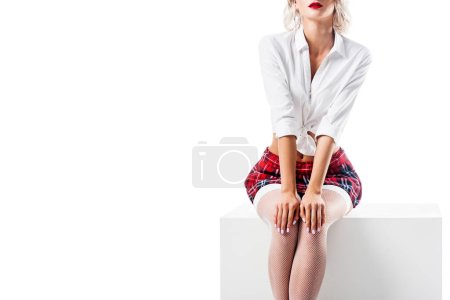 cropped shot of seductive woman in white shirt and plaid schoolgirl skirt sitting on white cube isolated on white