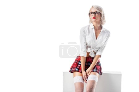 pensive and seductive woman in white shirt and plaid schoolgirl skirt sitting on white cube isolated on white