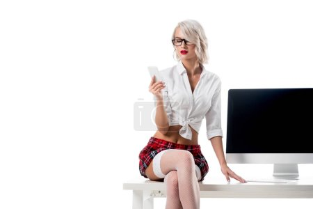 seductive schoolgirl in stockings with smartphone in hand sitting on table with blank computer screen isolated on white
