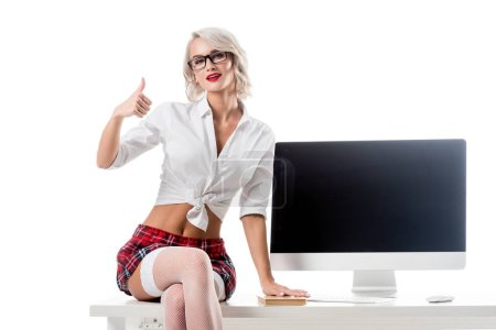 seductive schoolgirl in short plaid skirt showing thumb up while sitting on table with blank computer screen isolated on white