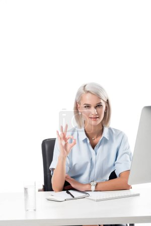 portrait of businesswoman showing ok sign at workplace with glass of water, notebook and computer screen isolated on white
