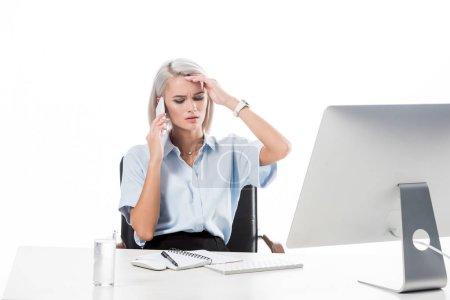 Photo pour Portrait de femme d'affaires fatigué de parler sur smartphone au lieu de travail avec le verre de l'eau, ordinateur portable et ordinateur écran isolé sur blanc - image libre de droit