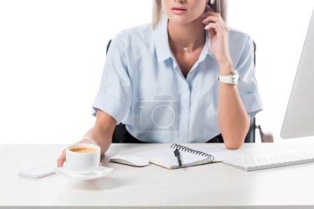 Photo pour Vue partielle de la femme d'affaires avec une tasse de café au lieu de travail avec écran pour ordinateur portable et ordinateur isolé sur blanc - image libre de droit