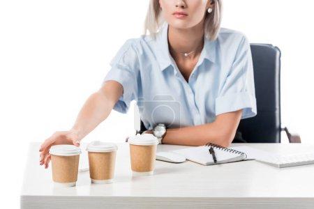 Photo pour Recadrée tir de femme d'affaires au lieu de travail avec des gobelets jetables de café et portable isolé sur blanc - image libre de droit