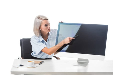 portrait of businesswoman pointing at blank computer screen at workplace isolated on white