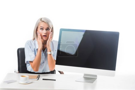 portrait of shocked businesswoman sitting at workplace with blank computer screen isolated on white