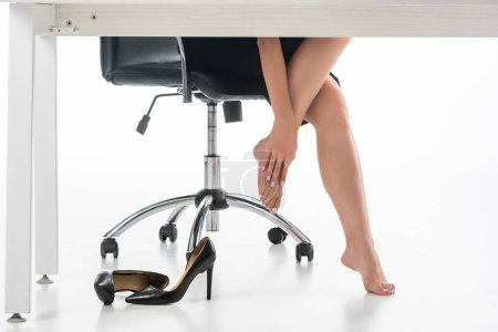 partial view of businesswoman sitting barefoot at workplace isolated on white
