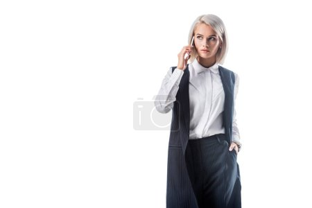 portrait of young businesswoman in formal wear talking on smartphone isolated on white