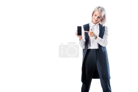 smiling businesswoman pointing at smartphone with blank screen in hand isolated on white