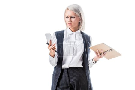 portrait of confused businesswoman with notebook looking at smartphone in hand isolated on white
