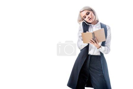 Photo pour Portrait de femme d'affaires, prendre des notes dans l'ordinateur portable tout en parlant sur smartphone isolé sur blanc - image libre de droit