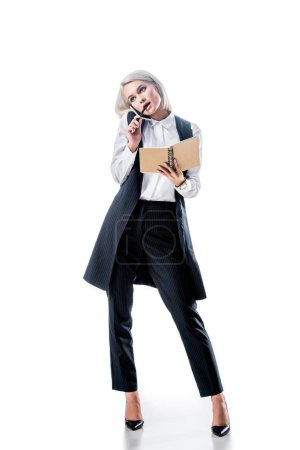 pensive businesswoman with notebook talking on smartphone isolated on white
