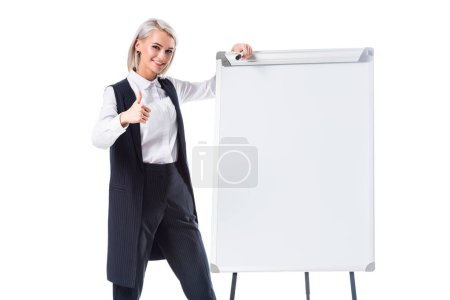 smiling businesswoman in formal wear near empty whiteboard showing thumb up isolated on white