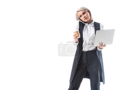 Photo for Portrait of busy businesswoman with coffee to go and laptop talking on smartphone isolated on white - Royalty Free Image