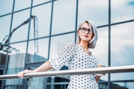 Photo for Portrait of stylish businesswoman in eyeglasses with coffee to go in hand looking away on street - Royalty Free Image