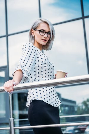 stylish businesswoman in eyeglasses with coffee to go in hand on street