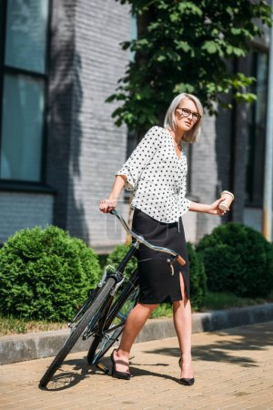 young businesswoman with coffee to go and retro bicycle on street