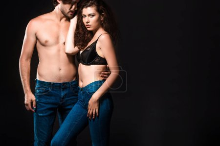 portrait of shirtless couple in jeans posing isolated on black
