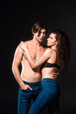 portrait of shirtless couple in jeans hugging isolated on black