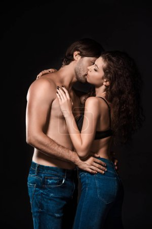side view of sexy shirtless couple kissing isolated on black