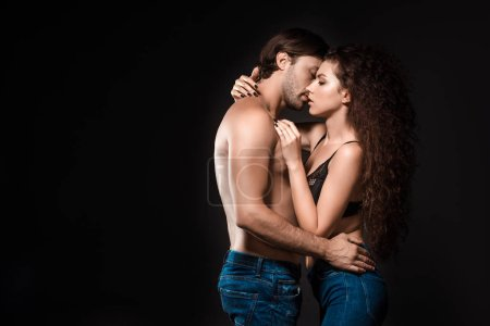 side view of sexy shirtless couple hugging and kissing isolated on black