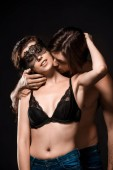 portrait of man hugging sexy shirtless girlfriend with black lace on eyes isolated on black
