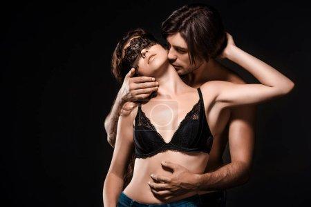 Photo pour Portrait de l'homme étreignant et embrassant sexy copine torse nu avec dentelle noire sur les yeux isolés sur noir - image libre de droit